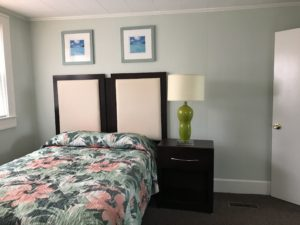 A lamp and table beside a floral bed