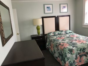 A dresser and table lamp beside a floral bed