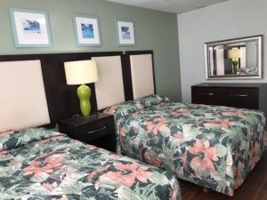 Two beds in front of a window and a dresser