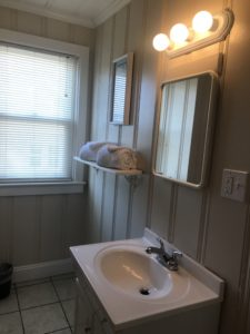 Two towels beside a bathroom sink and mirror
