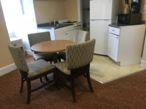 Dining table beside a refrigerator, an oven, and a microwave