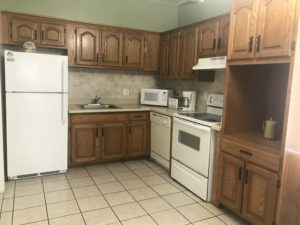 A kitchen with white and brown furniture