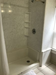 A shower with white flooring