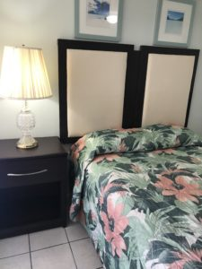 A lit table lamp beside a floral bed