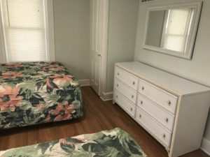 A white bedroom with white furniture