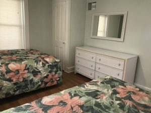 A white dresser in front of two floral beds