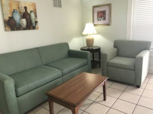 A living room with a table lamp in the corner
