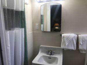 Two towels hanging beside a bathroom sink