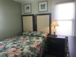 A floral bed with a padded headboard