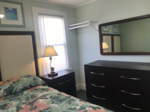 A bedroom with a dresser, a bed, and a mirror