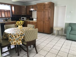 A sunflower dining table in front of a kitchen cabinet