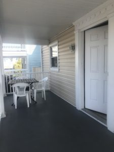 A table with two white chairs outside a door